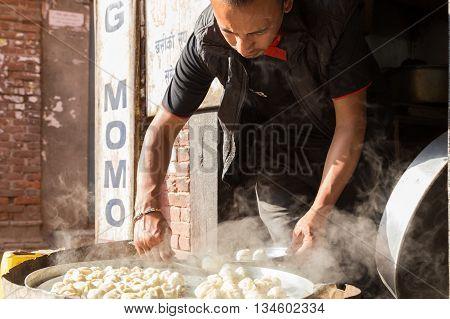 Bhaktapur, Nepal - December 4, 2014: Man preparing steamed Momos in the streets