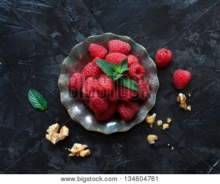 Raspberries walnuts and mint leaves on dark background top view