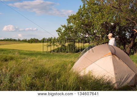 Camp in prairie in sunny day. Tents and hiker man on the background of prairie. Azov steppe Ukraine.