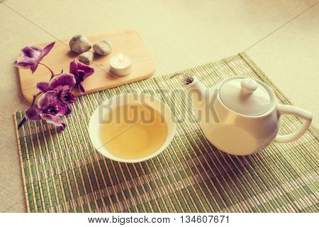 Still life with green tea in a cup and orchid branch among stones on a light background. Preparation for tea drinking. Tea ceremony. Toned image.
