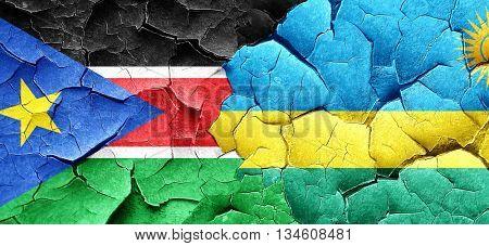 south sudan flag with rwanda flag on a grunge cracked wall