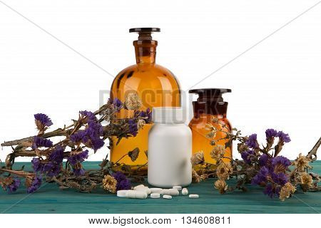 Medicine Bottles On Wooden Table Isolated With Flower And Pils
