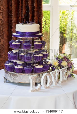 Purple and white wedding cake with matching cup cakes