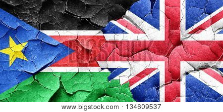 south sudan flag with Great Britain flag on a grunge cracked wal