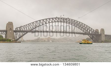 SYDNEY NSW/AUSTRALIA - NOV 3, 2015: Ferry boat motors past the Sydney Harbour Bridge on a misty morning in New South Wales Australia.