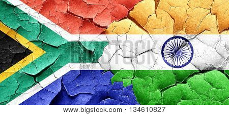 South africa flag with India flag on a grunge cracked wall
