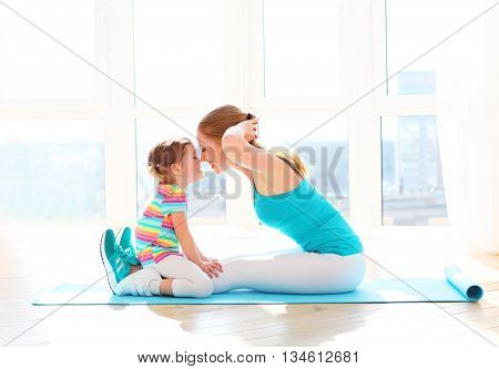 family mother and child daughter are engaged in fitness yoga exercise at home