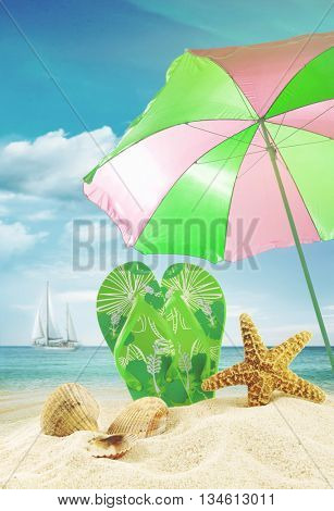 Sandals and seashells with beach umbrella at the ocean