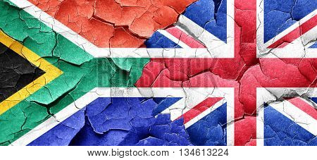 South africa flag with Great Britain flag on a grunge cracked wa