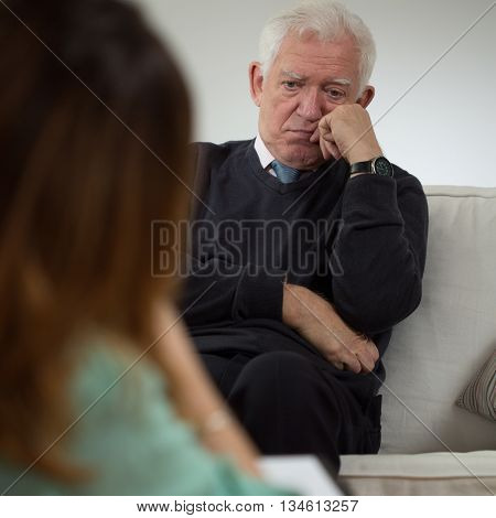 Elderly sad man talking with a psychotherapist