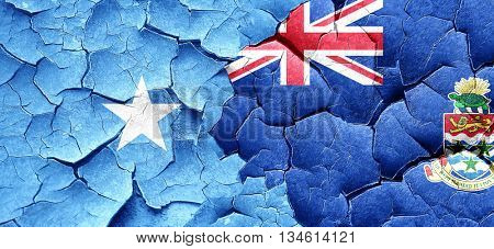 Somalia flag with Cayman islands flag on a grunge cracked wall
