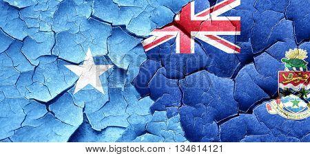 Somalia flag with Cayman islands flag on a grunge cracked wall
