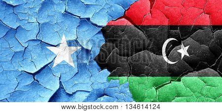 Somalia flag with Libya flag on a grunge cracked wall