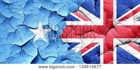 Somalia flag with Great Britain flag on a grunge cracked wall