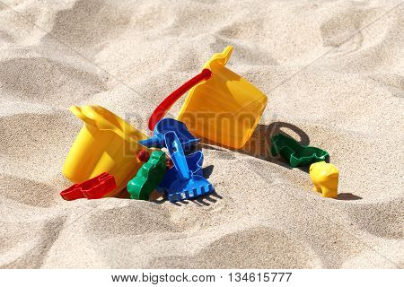 Plastic colored toys in the brown sand