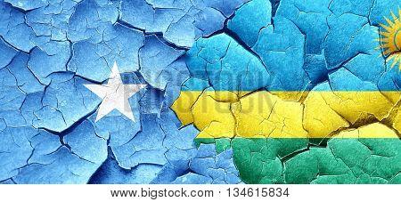 Somalia flag with rwanda flag on a grunge cracked wall