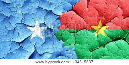 Somalia flag with Burkina Faso flag on a grunge cracked wall