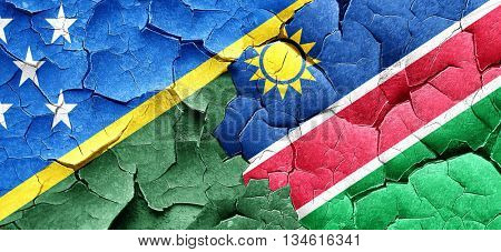 Solomon islands flag with Namibia flag on a grunge cracked wall