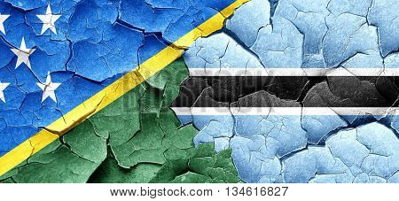 Solomon islands flag with Botswana flag on a grunge cracked wall