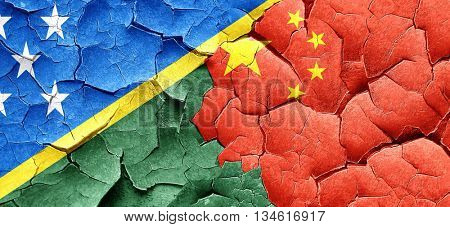 Solomon islands flag with China flag on a grunge cracked wall