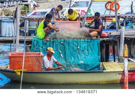 Labuan,Malaysia-June 16,2016:A local fishermen catching fish with the net, the traditional way of fishing at the small fishing at Labuan tropical island,Malaysia.
