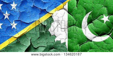 Solomon islands flag with Pakistan flag on a grunge cracked wall