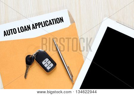 Top view of auto loan application in envelope with car remote key pen and tablet.