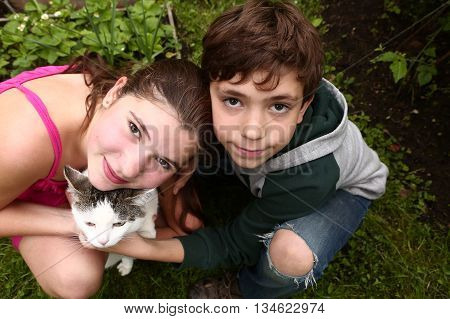 brother and sister siblings couple with siberian tom cat hug kiss close up portrait on the green summer grass background