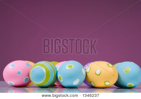Brightly Colored Easter Eggs On Pink Background