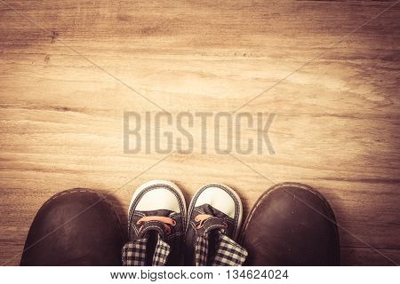 Daddy's boots and baby's sneakers on wood background fathers day concept.vintage color