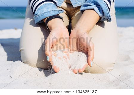 Woman In Denim Jacket Sits On A Beach With Sand In Her Hands