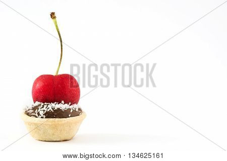 Delicious chocolate tartlets with cherry and coconut isolated on white background