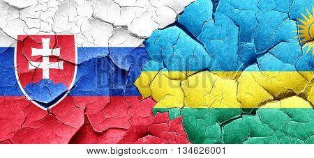 Slovakia flag with rwanda flag on a grunge cracked wall