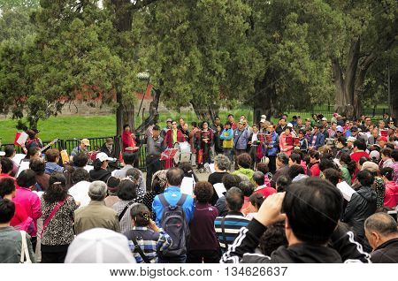 April 26, 2016. Temple of Heaven Park, Beijing China.  A crowd of Chinese people gathered around a band performing tradtional chinese songs within the Temple of Heaven park in Beijing China.