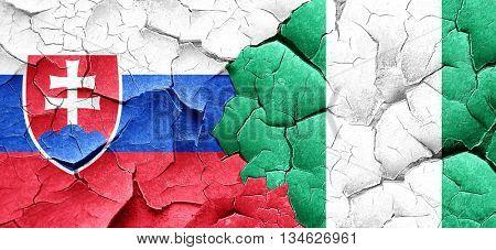 Slovakia flag with Nigeria flag on a grunge cracked wall
