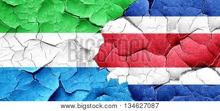 Sierra Leone flag with Costa Rica flag on a grunge cracked wall