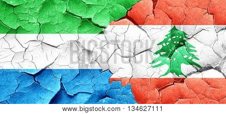 Sierra Leone flag with Lebanon flag on a grunge cracked wall