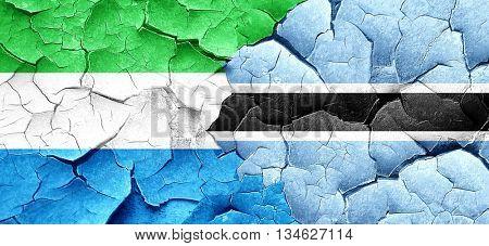 Sierra Leone flag with Botswana flag on a grunge cracked wall