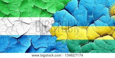 Sierra Leone flag with rwanda flag on a grunge cracked wall