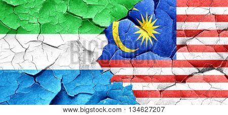 Sierra Leone flag with Malaysia flag on a grunge cracked wall