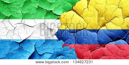 Sierra Leone flag with Colombia flag on a grunge cracked wall