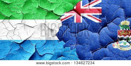 Sierra Leone flag with Cayman islands flag on a grunge cracked w