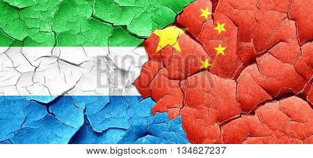 Sierra Leone flag with China flag on a grunge cracked wall
