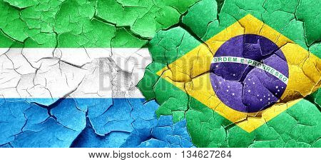 Sierra Leone flag with Brazil flag on a grunge cracked wall