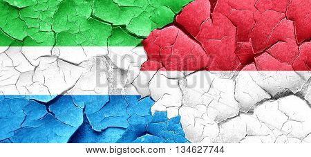 Sierra Leone flag with Indonesia flag on a grunge cracked wall