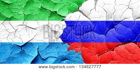Sierra Leone flag with Russia flag on a grunge cracked wall