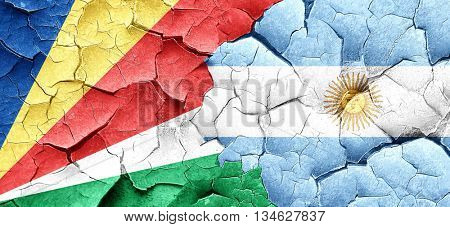 seychelles flag with Argentine flag on a grunge cracked wall