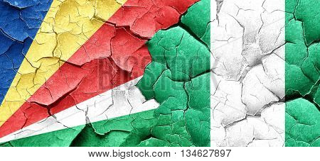seychelles flag with Nigeria flag on a grunge cracked wall