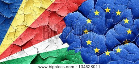 seychelles flag with european union flag on a grunge cracked wal