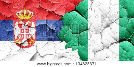 Serbia flag with Nigeria flag on a grunge cracked wall